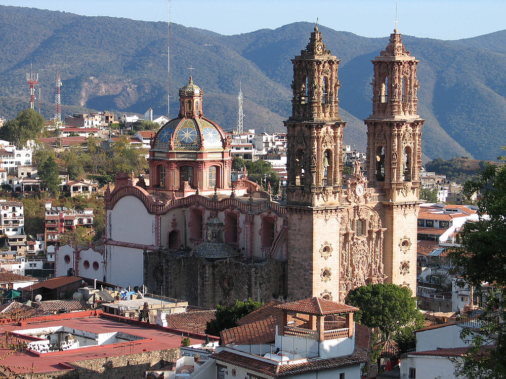 Ornate baroque church with two towers and a dome, mountains in back