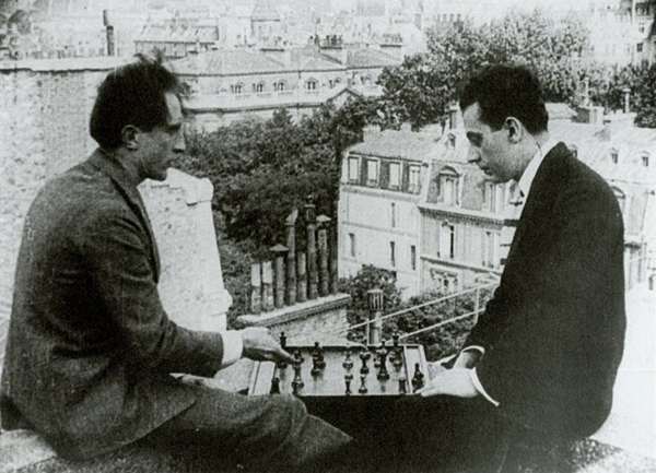 Film still of Marcel Duchamp and Man Ray playing chess on a rooftop in Paris.