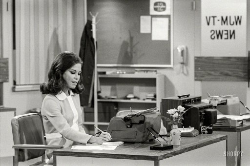 Mary Tyler Moore as Mary Richards working at her desk in a newsroom