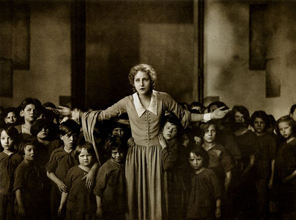 Sepia film still of woman surrounded by children