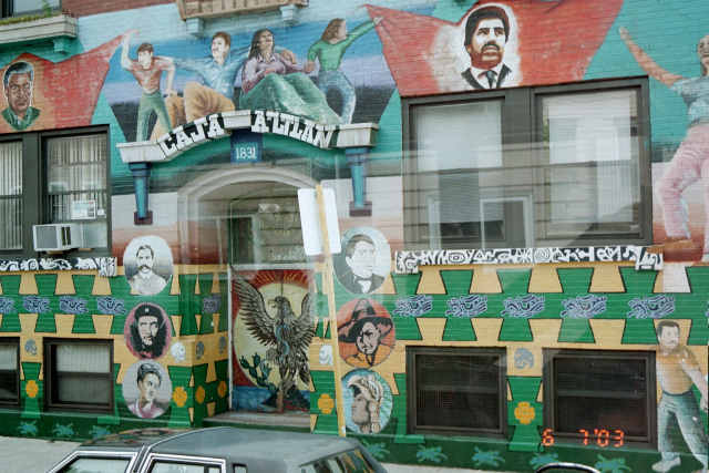 Mural with Chicano imagery painted on building facade.