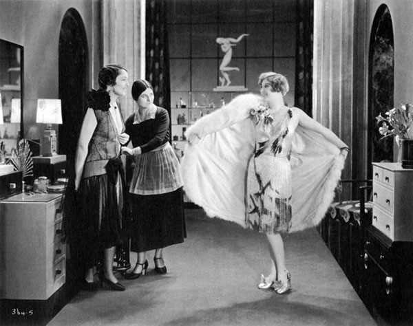 Woman displaying outfit to two others in art deco interior
