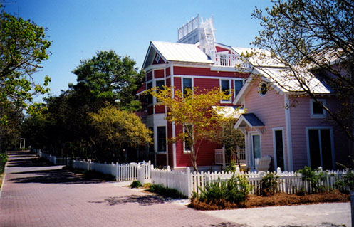 Pink and red houses with picket fence and walkway