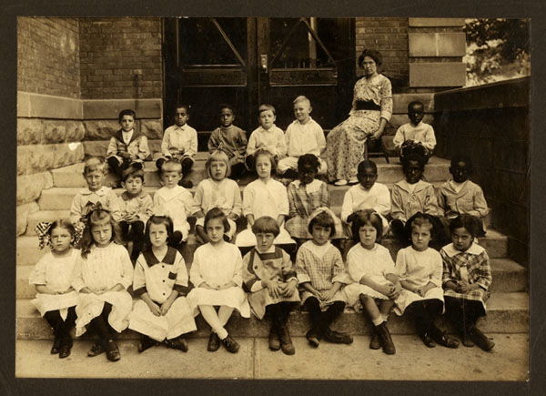 Group of children and teacher sitting outside their school
