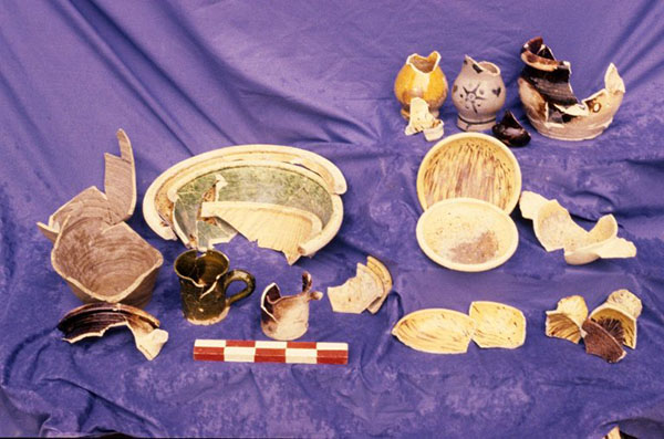 Various broken ceramic objects including plates and mugs