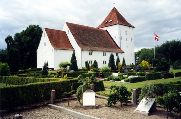 White church with pitched roof and steeple in front of cemetery