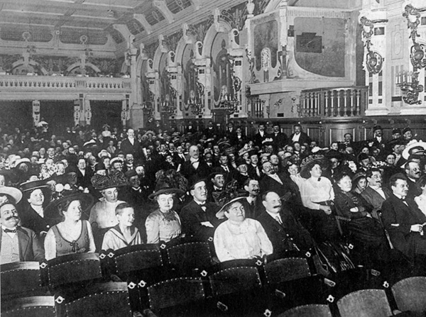 German audience wearing 1913 era clothes, inside an ornate theater.