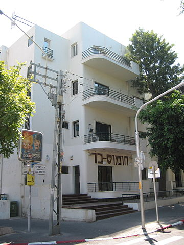 Modern white building with balconies on facade.