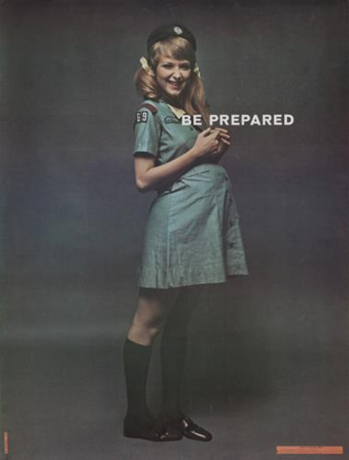 """Woman dressed as a Girl Scout, pregnant, with """"Be Prepared"""" on the poster."""