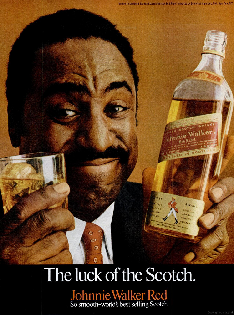 Black man holding a glass and bottle of Johnnie Walker scotch
