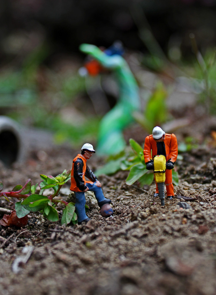 photograph of two tiny plastic toy workmen figurines - one operating a jackhammer as the other watches on - standing on dirt on the ground. Plants, trash, and other items appear nearby and in the background.