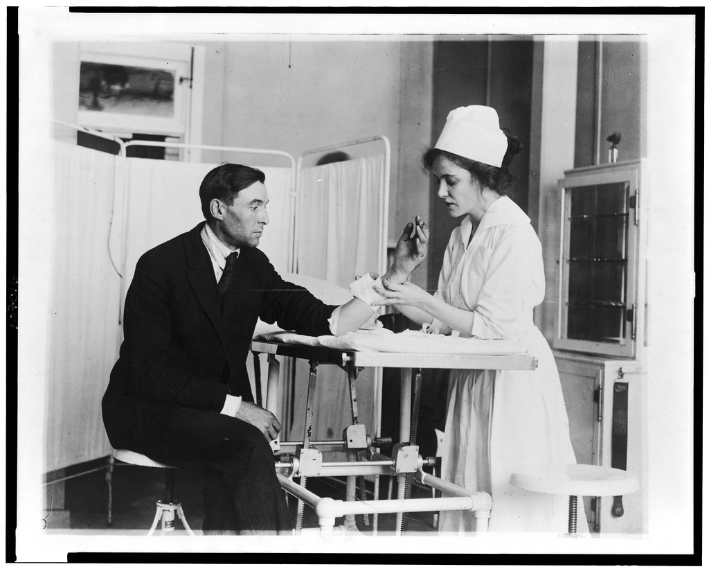 black and white photo of a nurse treating a patient