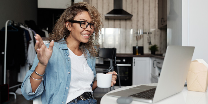 Woman on video call laughing with a cup of coffee