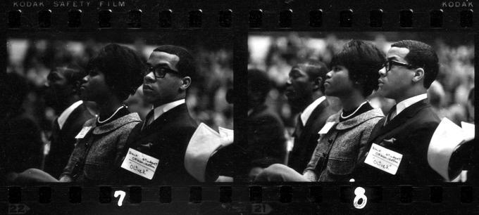 Black and white image of a negative, showing two different shots of the same couple seated in a crowd.