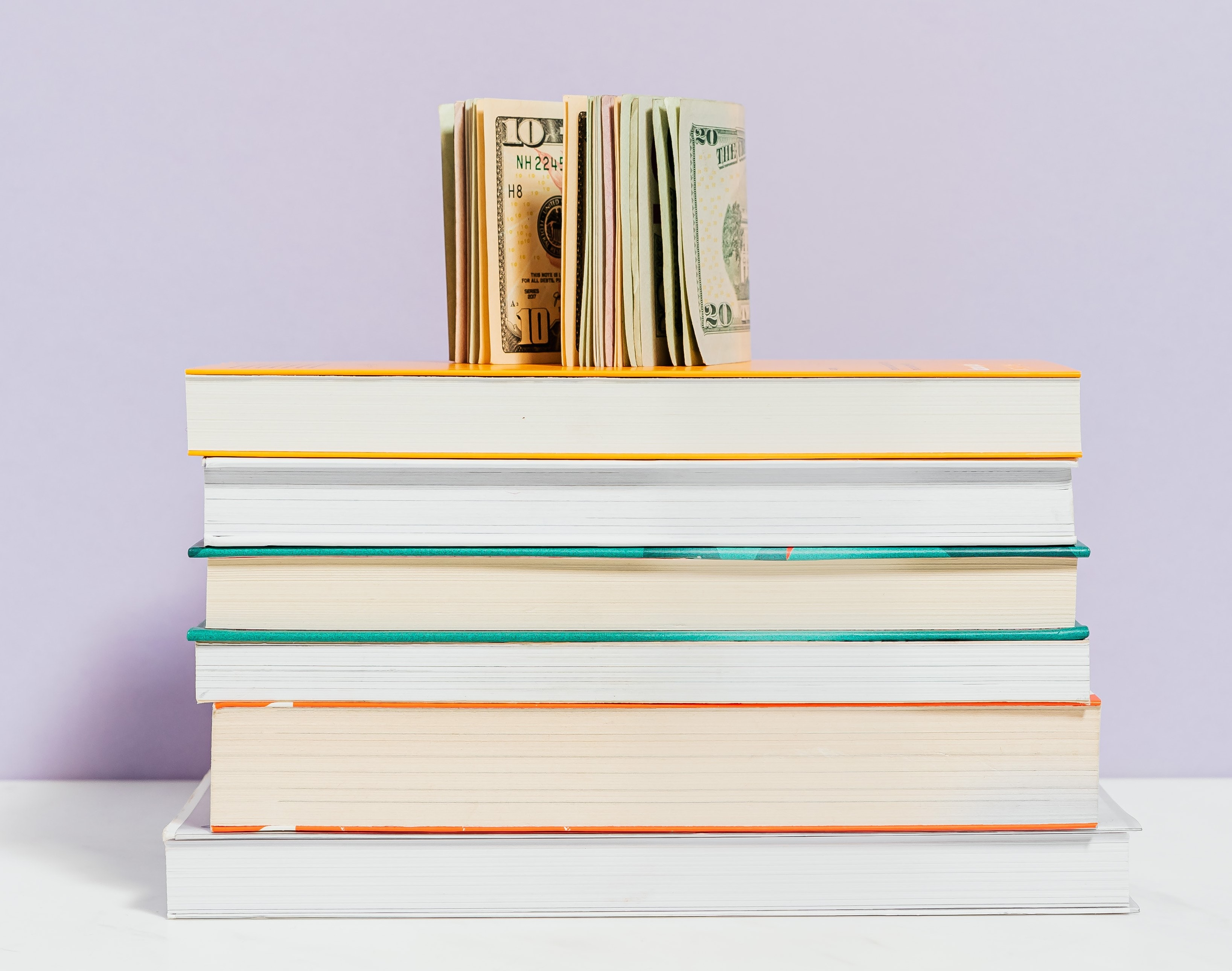 Stack of books with a roll of ten dollar bills on top