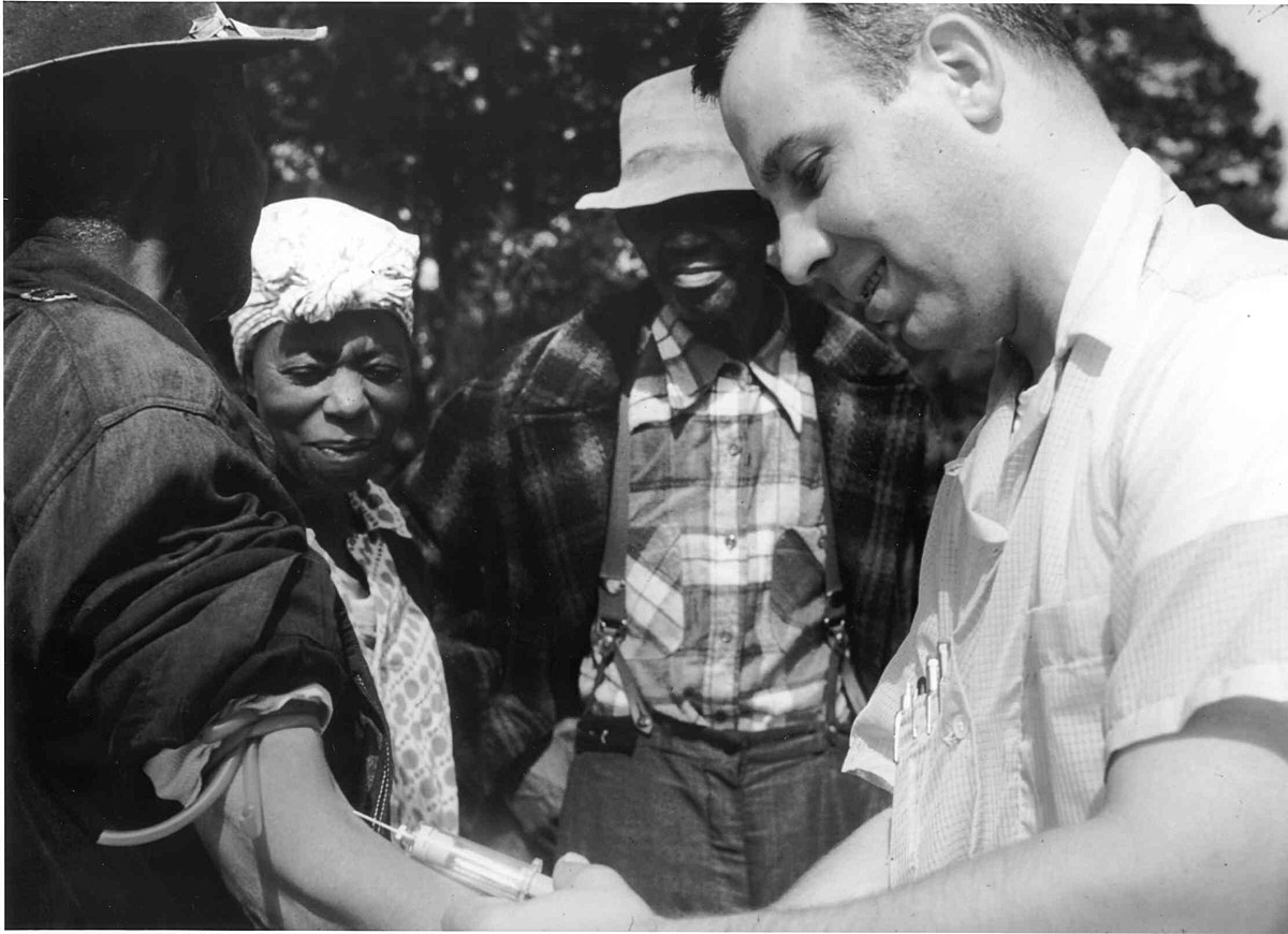 Black and white photo of a doctor drawing blood from a patient as part of the Tuskegee Syphilis Study