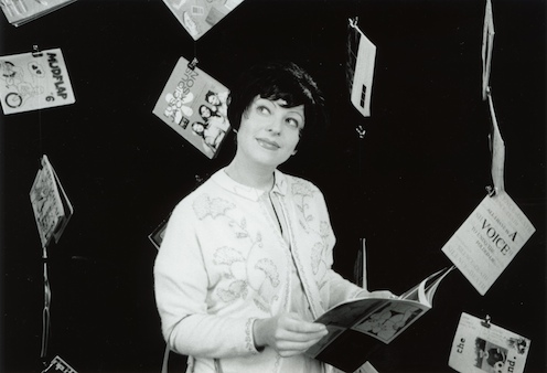 still black-and-white image from the dvd showing a woman smiling at the camera with zines hung about her