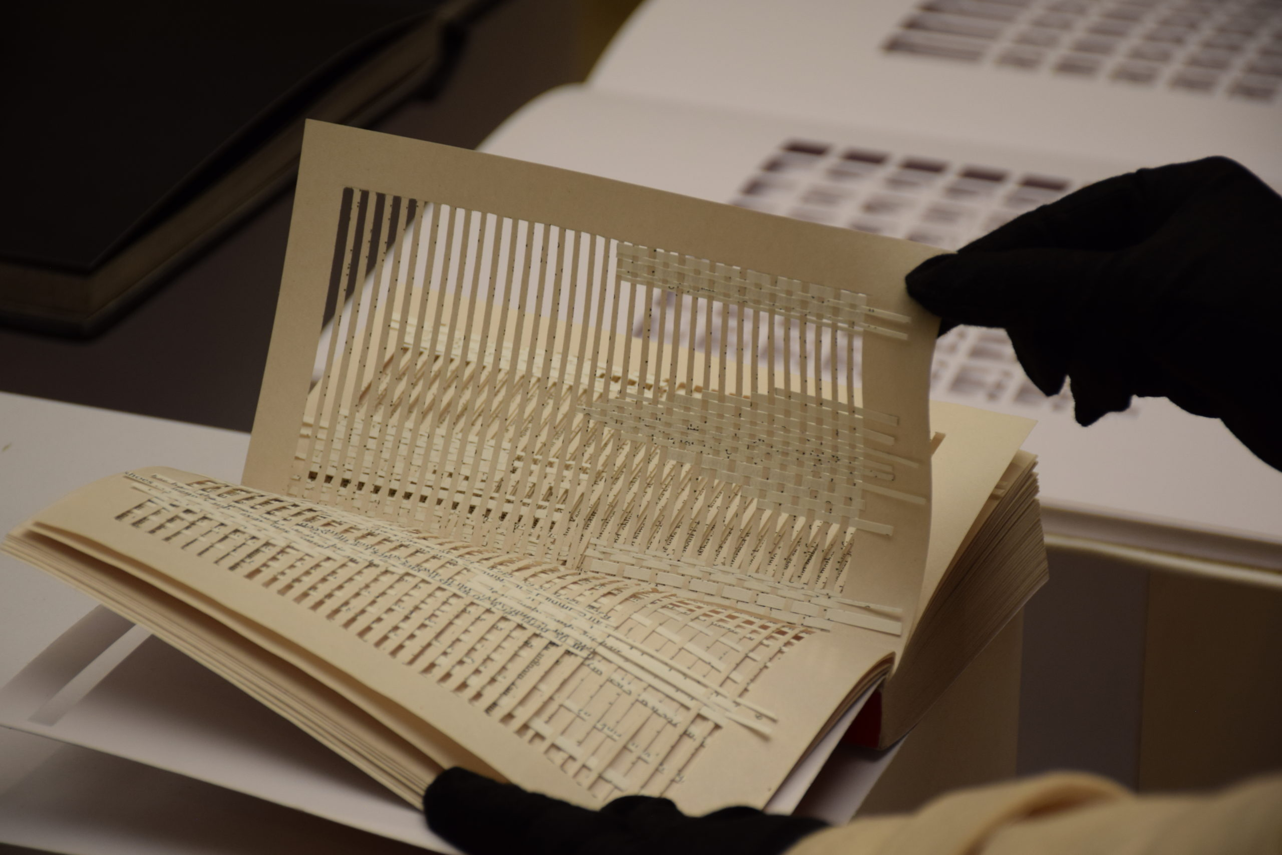 An open artists' book by Masoumeh Mohtadi being paged through by a black gloved hand showing pages with excised text and woven bits of paper throughout