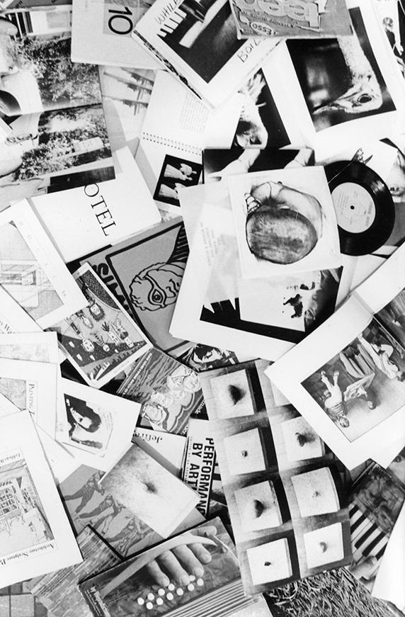 black and white overhead shot of a pile of booklets and magazines