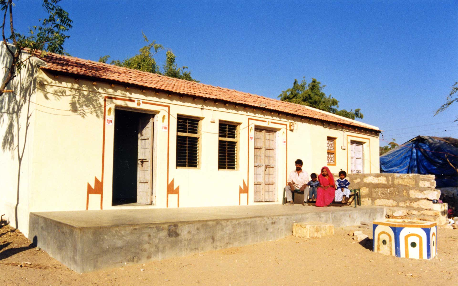 One of the homes in the Bhadli Village with a family sitting in front of it
