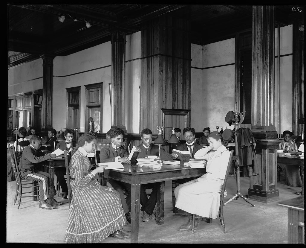 Library reading room with male and female students sitting at tables, reading, at the Tuskegee Institute