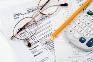 glasses on top of IRS tax forms and reciept next to a yellow pencil and calculator