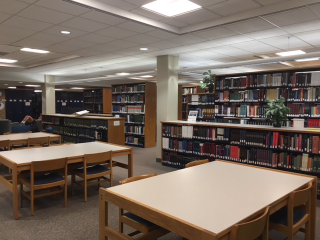 View of Hekman Reference Collection, showing tables in foreground, short and tall stacks of books behind