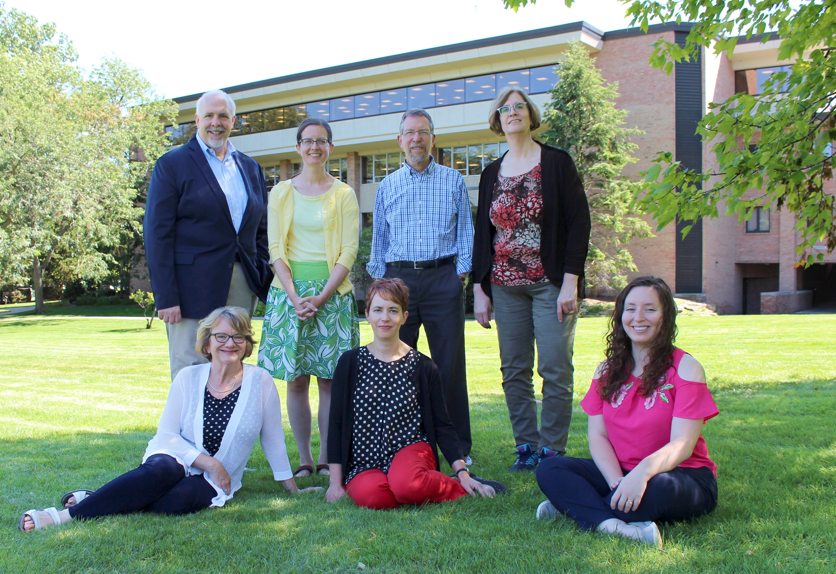 Color photo of Calvin research librarians, in front of Hekman Library building