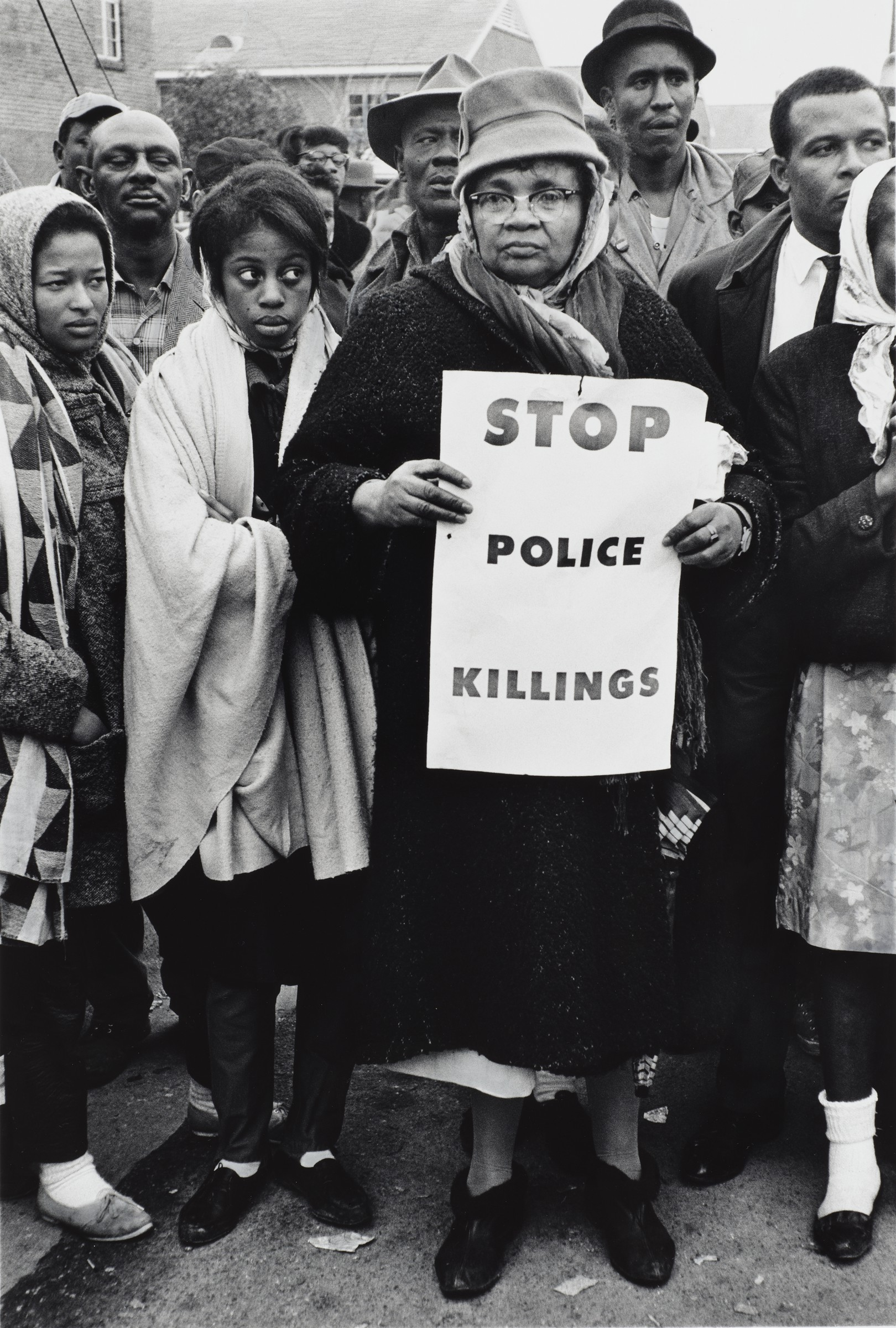 "Image of a group of African American citizens in Alabama in 1965; the woman in front is holding a sign that says, ""Stop Police Killings"""