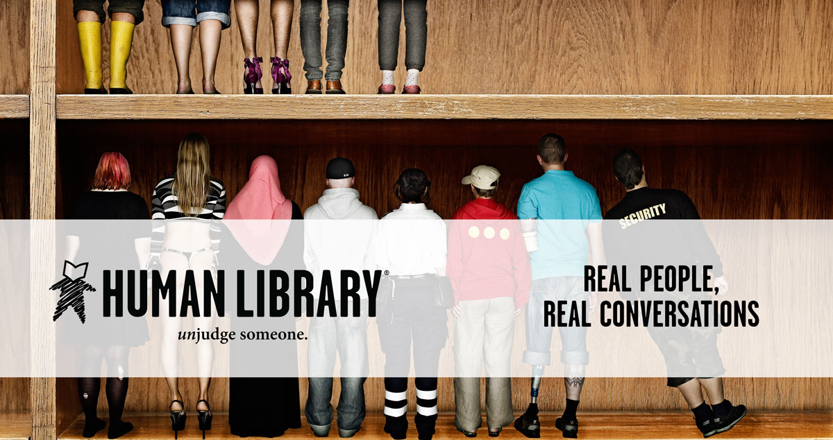 People Standing Next to Each Other on a Book Shelf