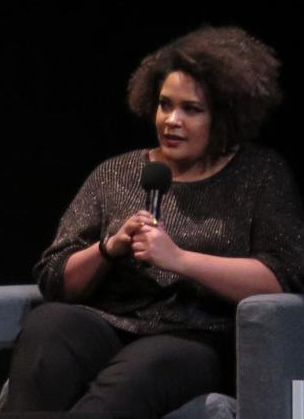 Photo of Iljeoma Oluo, seated, with microphone
