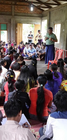 Photo of migrant workers in Burma listening to speaker
