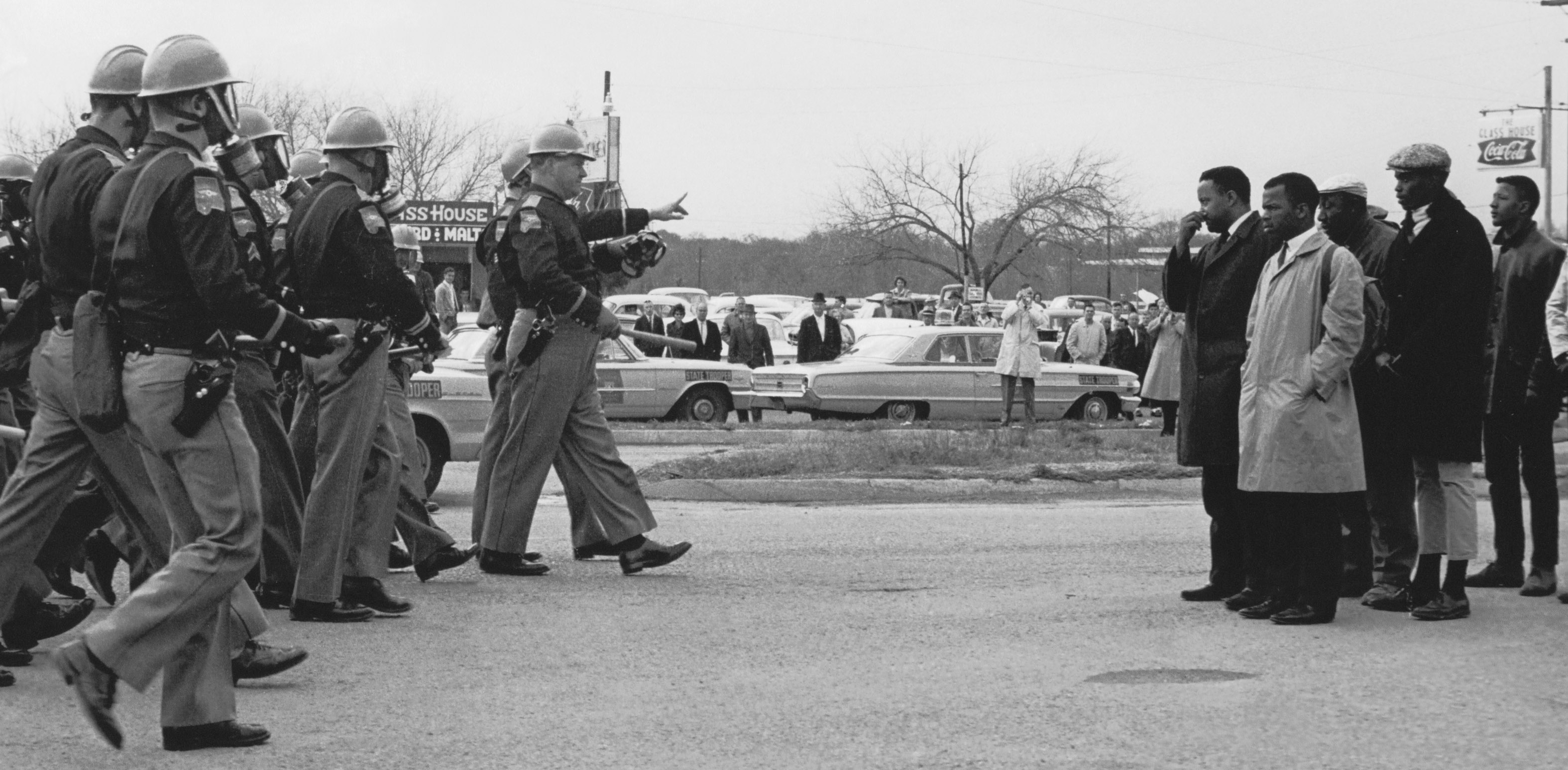 black and white photo of police officers facing a group of black men