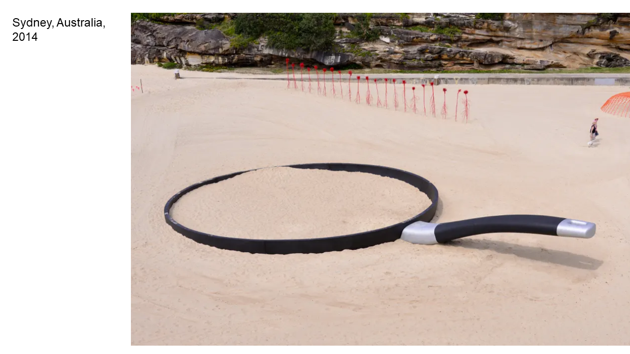This is a photo of a giant frying pan on a beach, labeled Sydney, Australia, 2014.