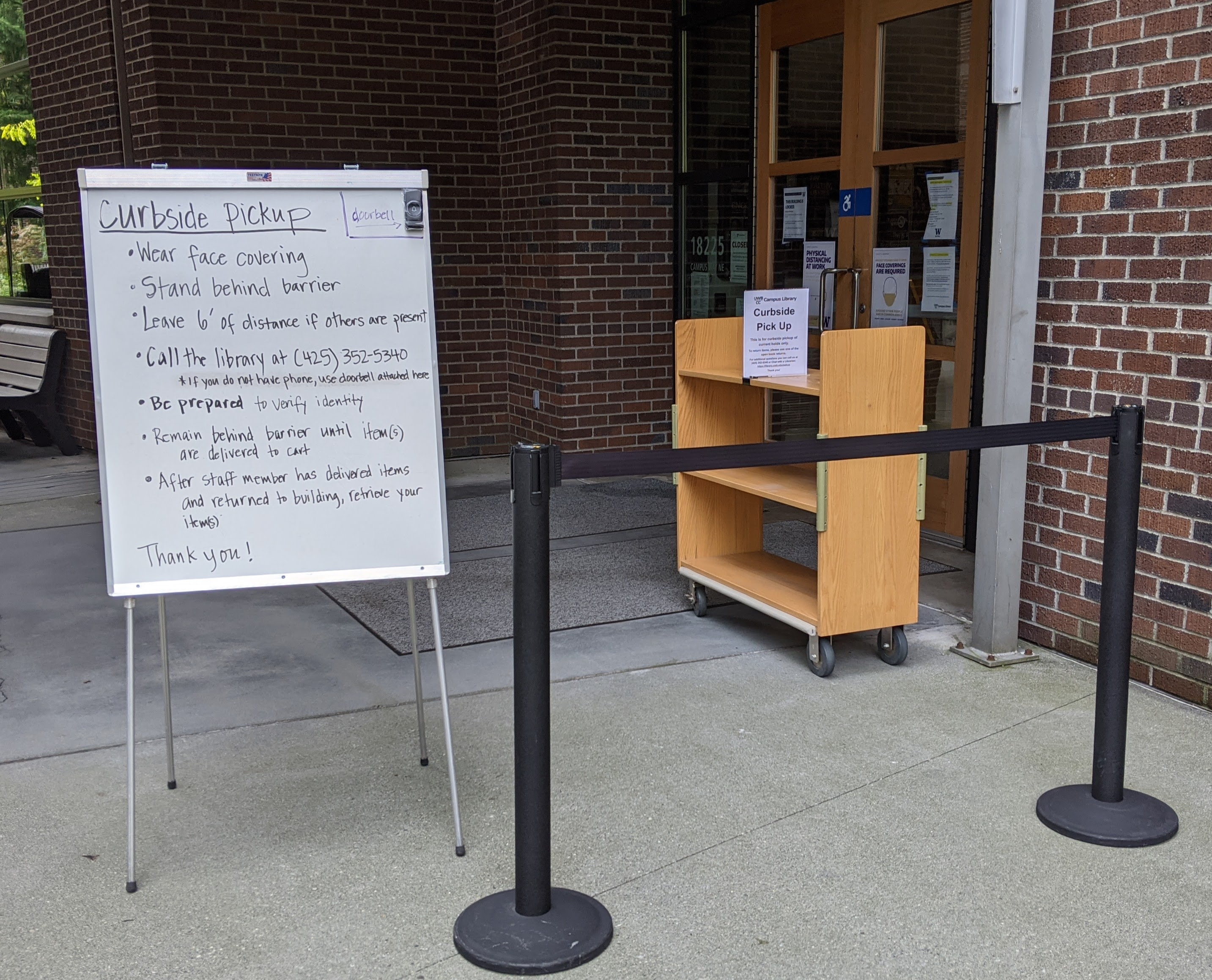 photograph of rolling cart, sign, and barrier outside library doors for contact-free pickup