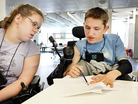 2 students in wheelchairs working on a paper