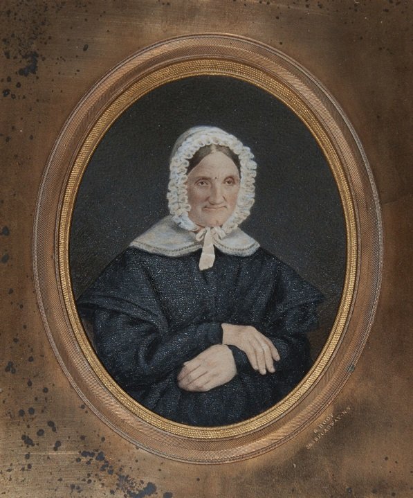 daguerreotype of a seated white woman in a white bonnet wearing a dark dress, and with her hands folded