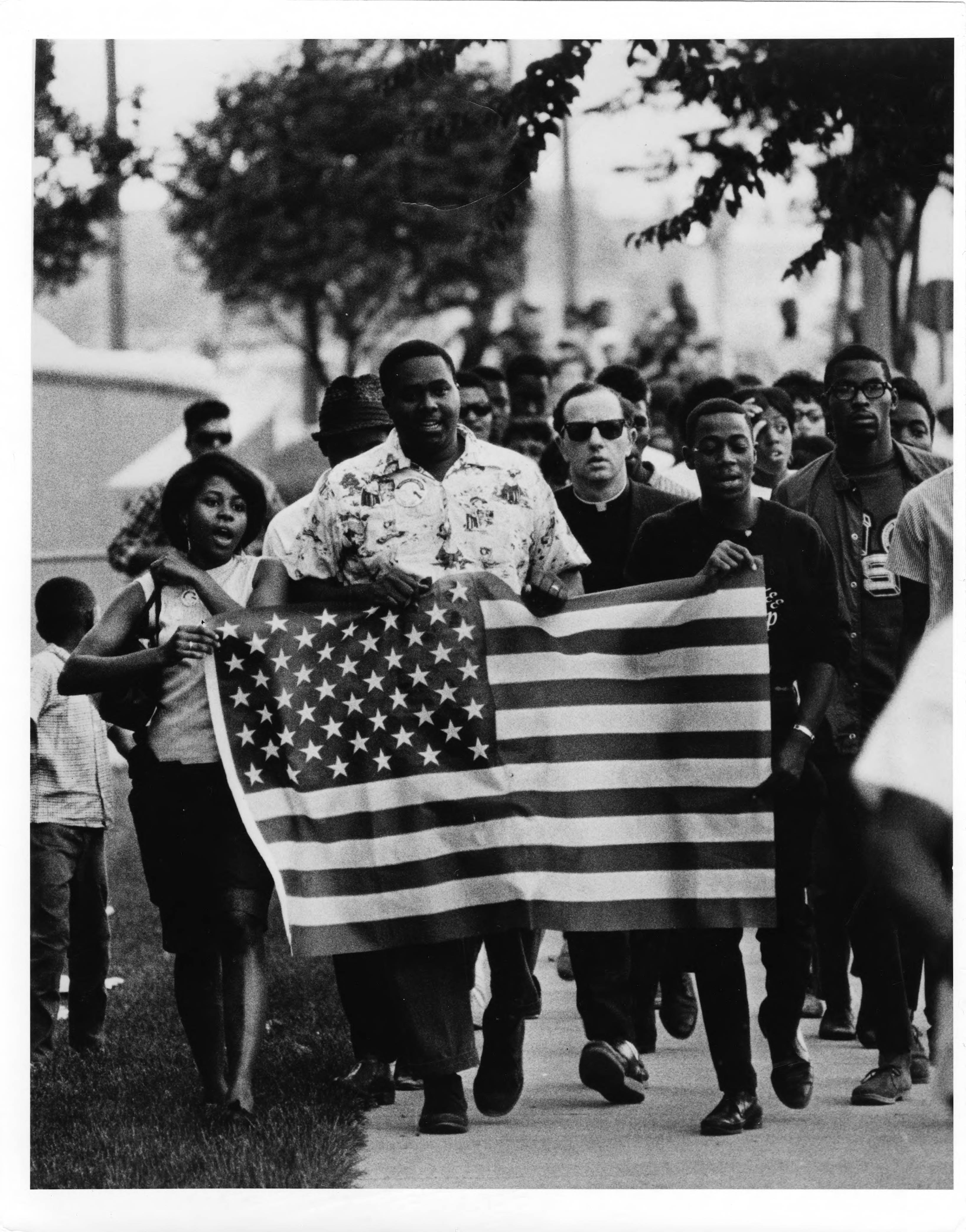 image of Eagles Club protest in the 1960s. Civil rights marchers fill a street and hold an American Flag