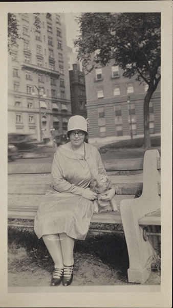 Elise Rocheleau sitting on a park bench with an unidentified dog.