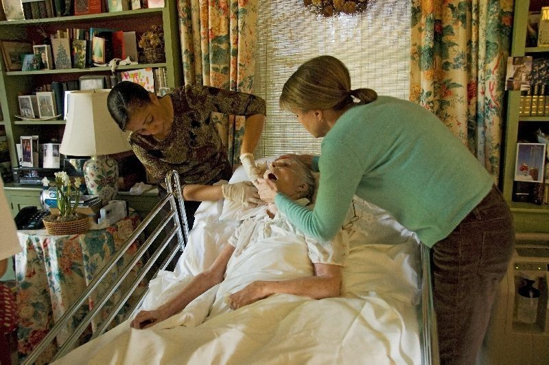 Hospice nurses caring for a woman during her last hours of life