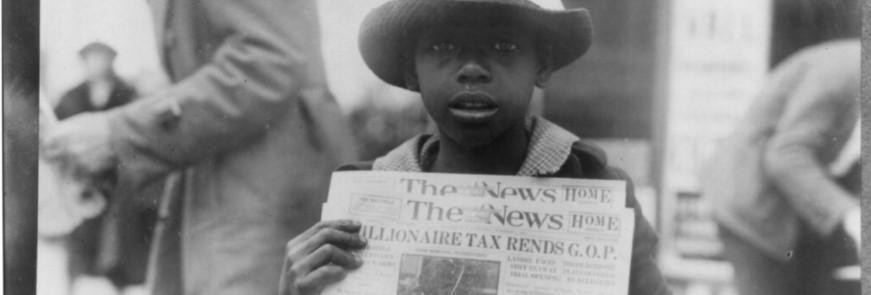 African American teenager selling newspapers