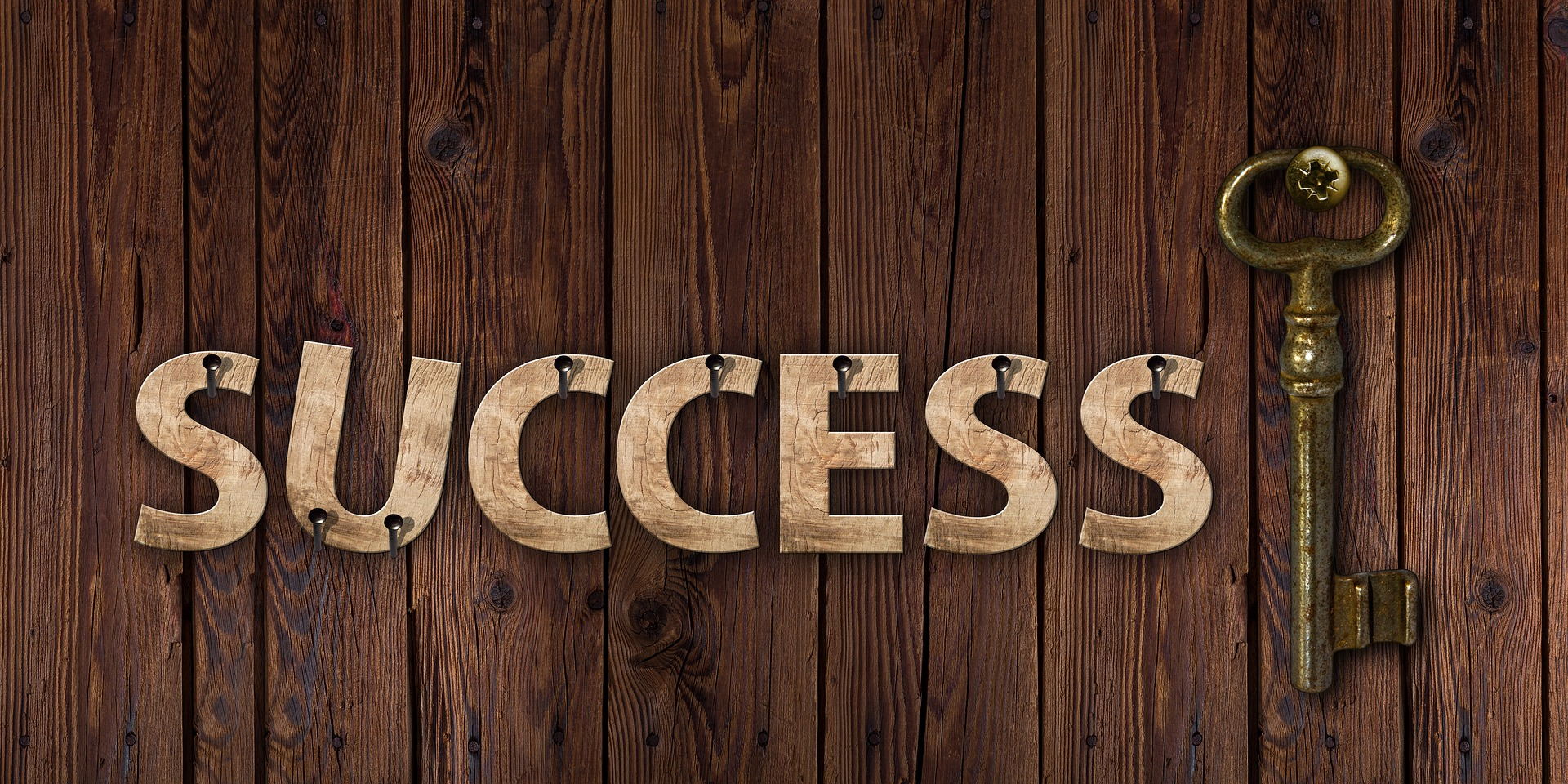 Success written out with a key on planks of wood