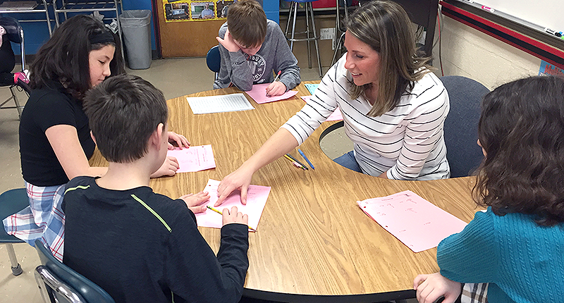 Mrs. Barry meets with her 6th-grade math students to review their work.