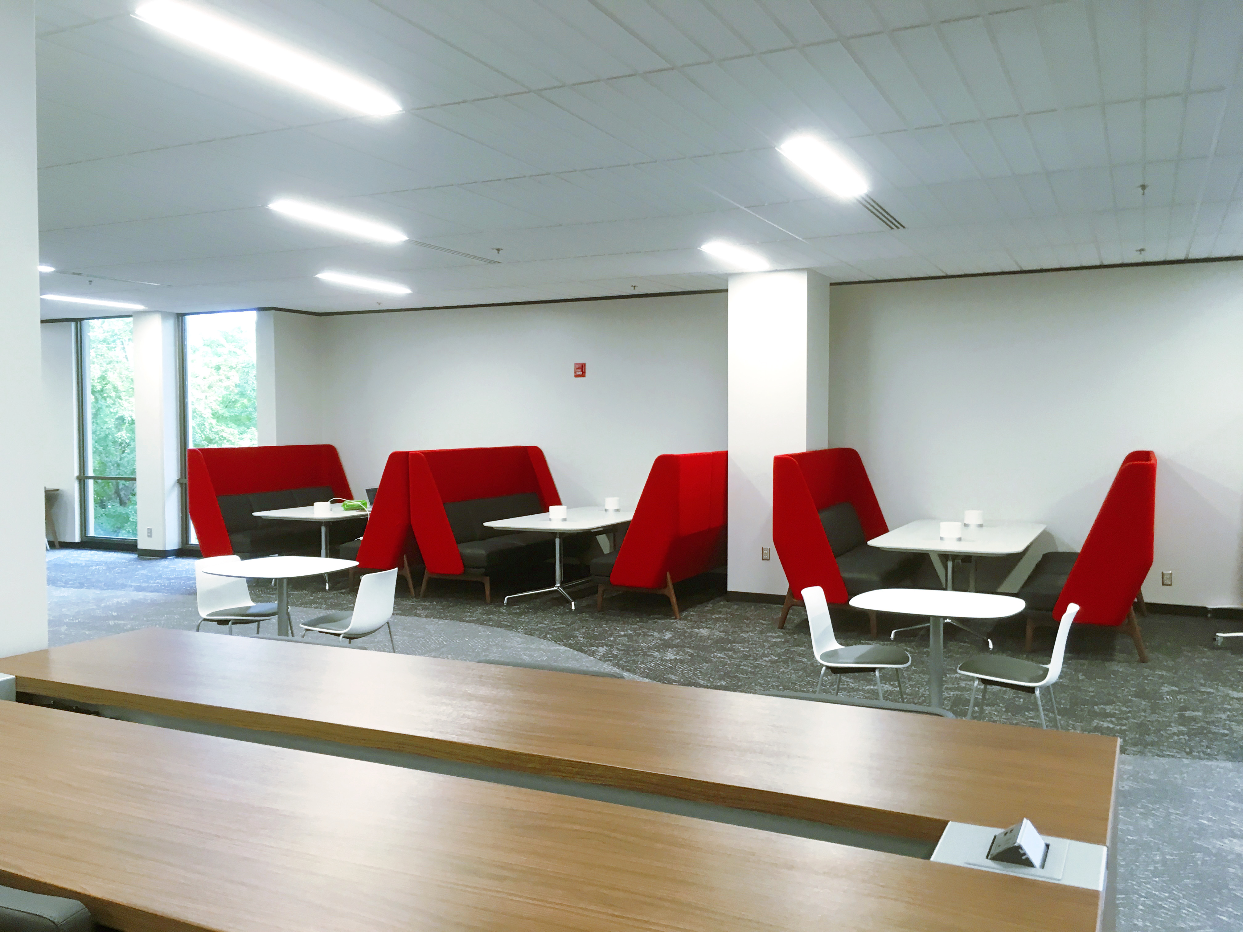 Study space on second floor in Learning Commons showing booths and tables