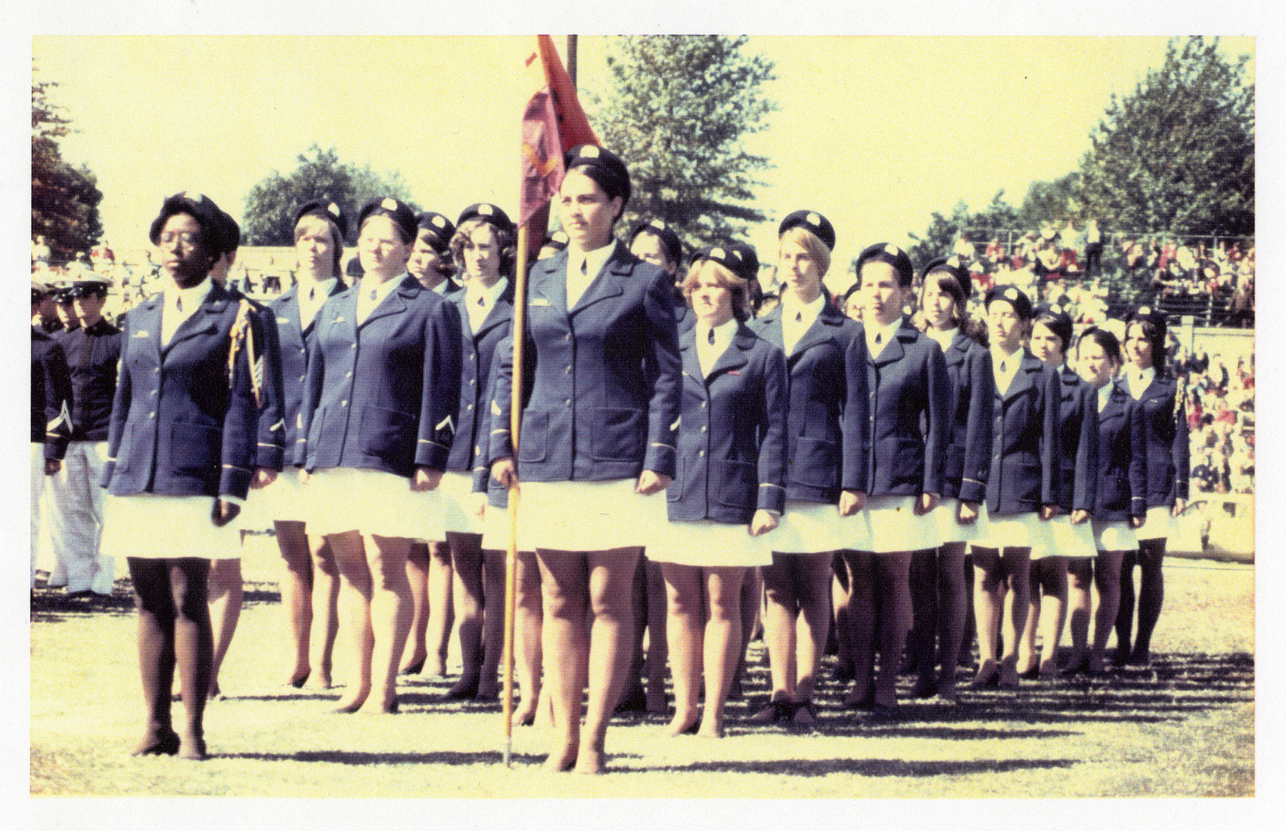 Uniformed women of L Squadron standing at attention in formation, circa 1970s.