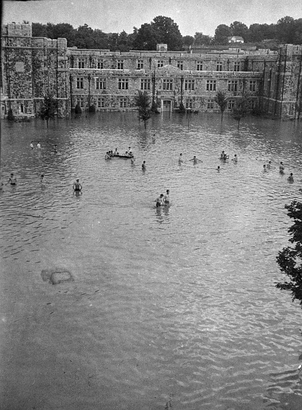 Flooded Eggleston Quad with shirtless students wading and boating in the flood waters.