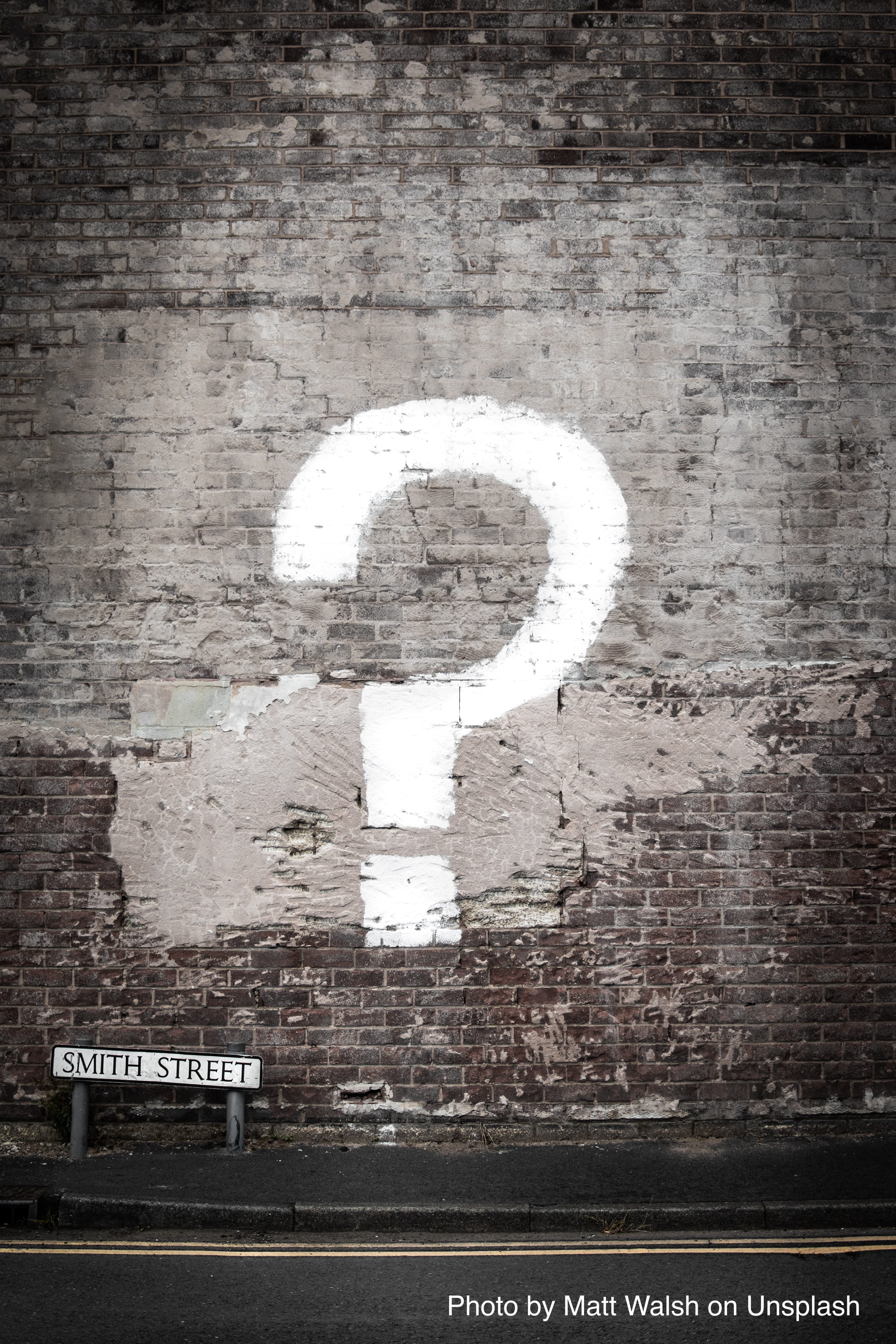 white question mark painted on brick wall photo