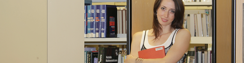 Female student holding book in the ACC Library.