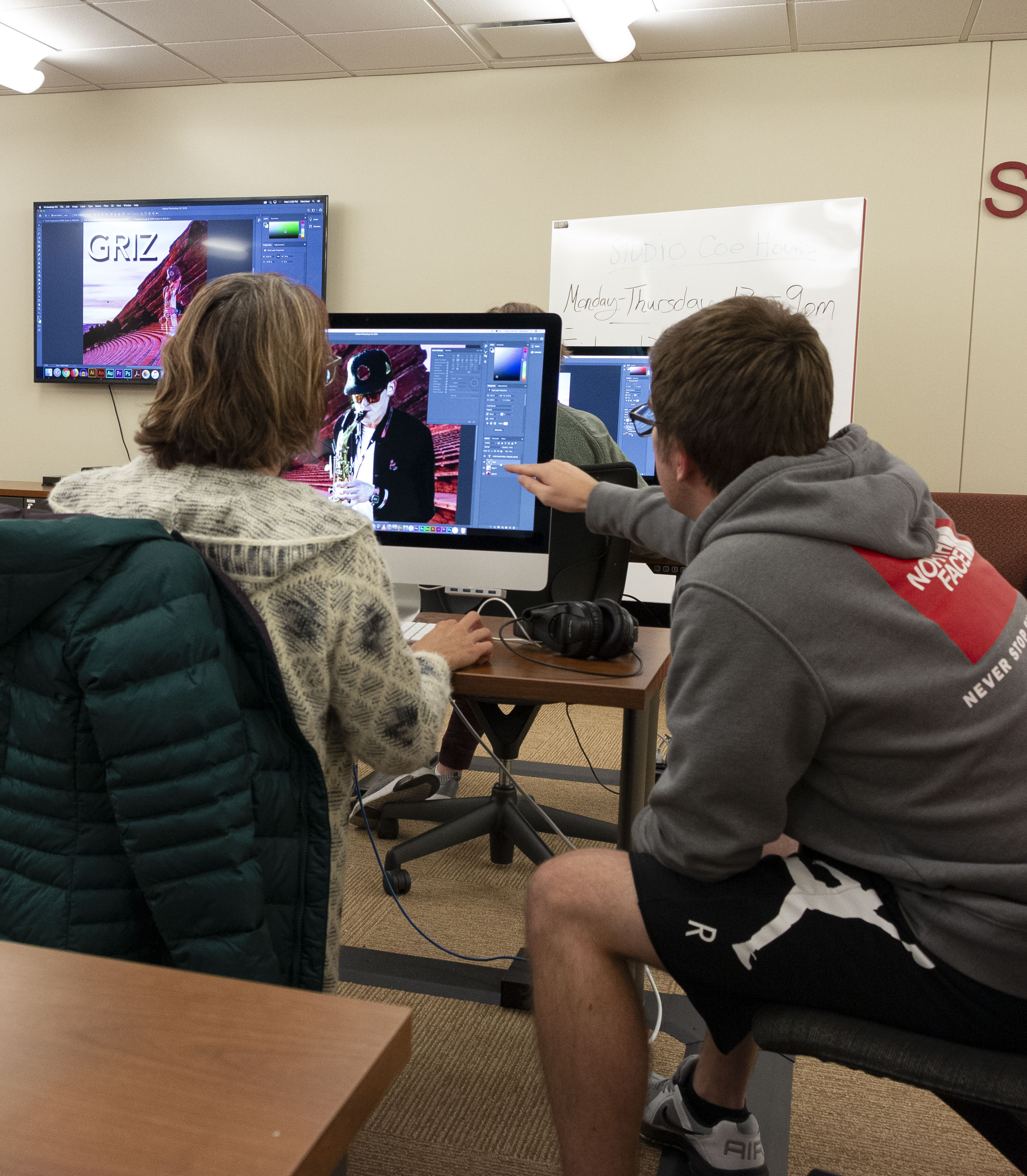 A student staff member is helping a patron use Photoshop.