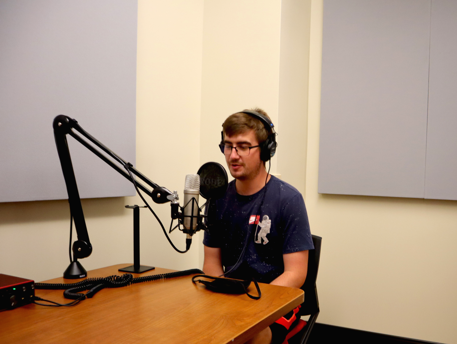 student sitting in front of a microphone